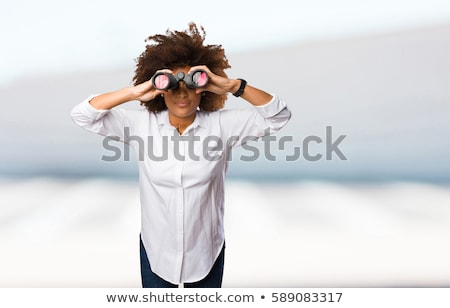 Young woman spy looking through binoculars stock photo © darrinhenry