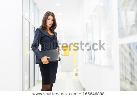 A portrait of a young business woman in a hall of an office buil stock photo © HASLOO