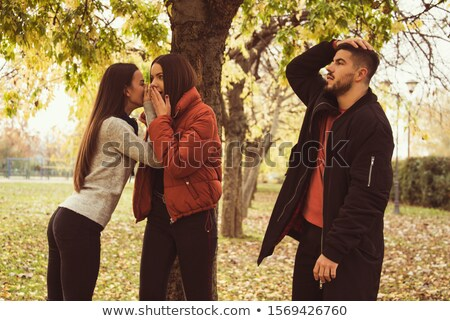 Young women whispering behind another woman's back Stock photo © photography33