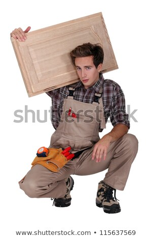 portrait of young cabinetmaker carrying cupboard door over shoulder Stock photo © photography33