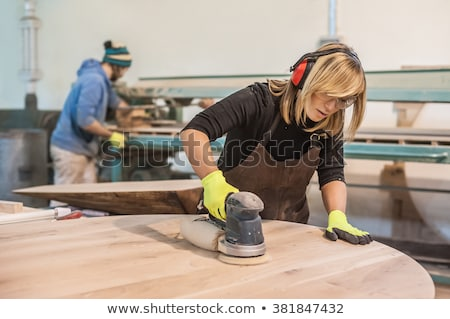 Stock photo: A female carpenter sawing.