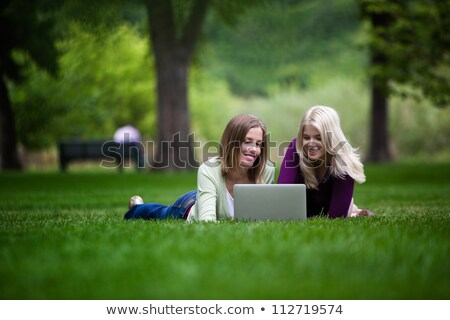 Blonde woman using a laptop on the grass Stock photo © stryjek