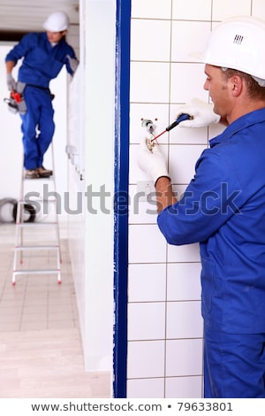 an electrician screwing an electrical outlet and a colleague on a stepladder Stock photo © photography33