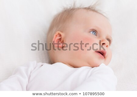 Cute little baby looking towards the side while lying on a blanket stock photo © wavebreak_media