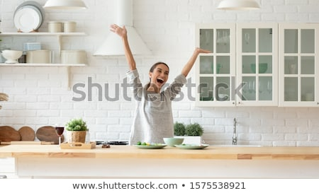 Young woman in good mood standing in kitchen singing Stock photo © serendipitymemories