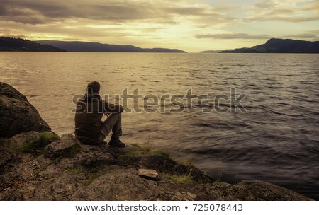 Man sitting on a rock by the sea Stock photo © Kotenko