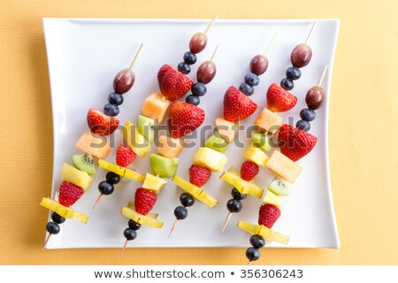 Fresh fruit shish kebabs on a modern square plate Stock photo © ozgur