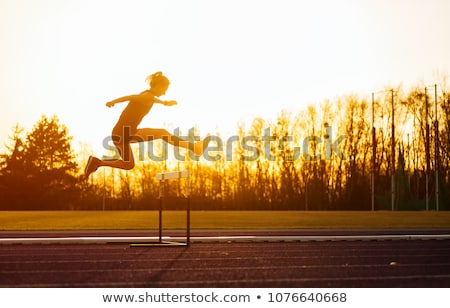 Girl jumping hurdles on track Stock photo © bluering