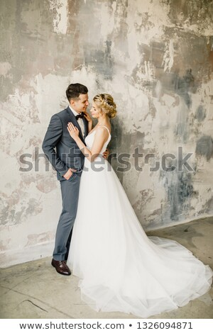 young wedding couple kissing against a gray wall stock photo © artfotodima