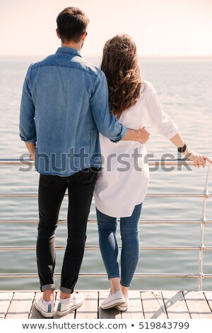Young couple standing backwards hugging and looking at the seaside Stock photo © deandrobot