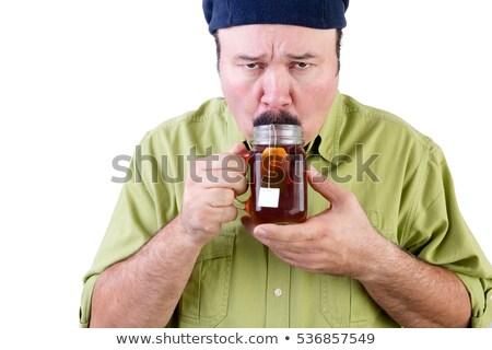 Unsure man tasting cup of herbal tea on white Stock photo © ozgur