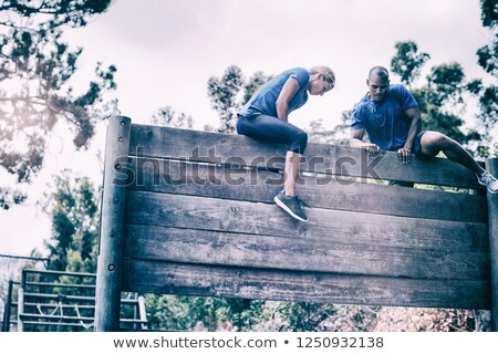 Determined woman climbing wooden wall during obstacle course Stock photo © wavebreak_media