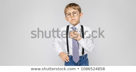 A charming boy in a white shirt, suspenders, a tie and light jeans stands on a gray background. Boy  Stock photo © Traimak