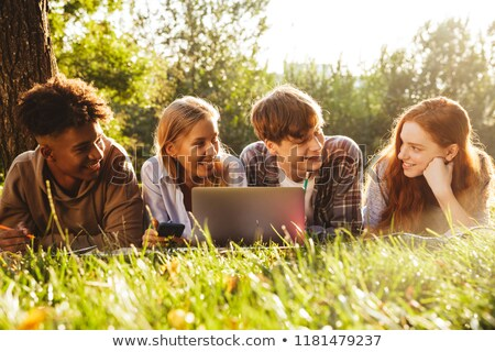 group of excited multhiethnic students doing homework stock photo © deandrobot