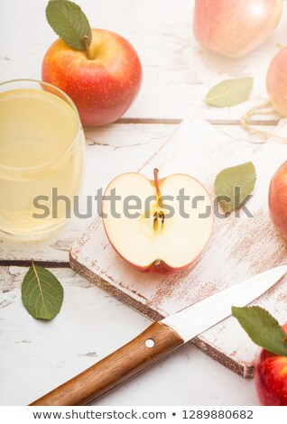 Glass of fresh organic apple juice with pink lady red apples on chopping board on wooden background  Stock photo © DenisMArt