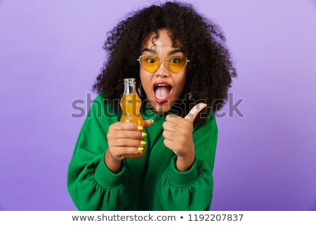 Amazing pretty african woman isolated over violet background showing thumbs up gesture drinking soda Stock photo © deandrobot