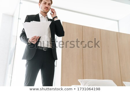 image of brunette man 30s in business suit holding black mobile stock photo © deandrobot