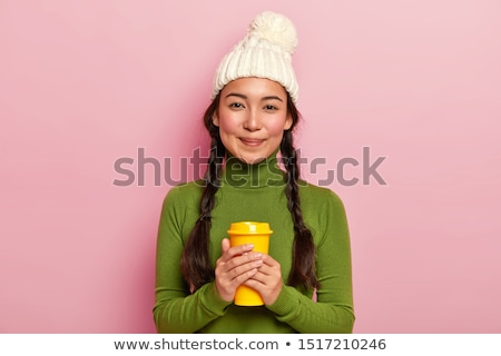 Stock photo: Image of two positive women wearing hats holding takeaway coffee