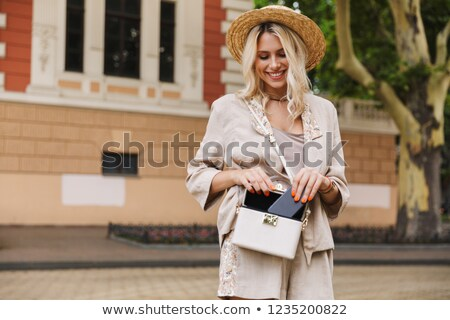 Image of caucasian lady wearing suit and straw hat smiling, whil Stock photo © deandrobot
