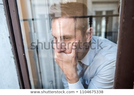 man close to a window looking sad stock photo © lopolo