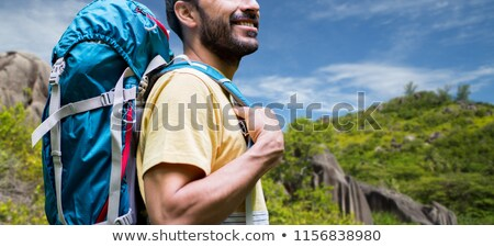 close up of man with backpack over seychelles stock photo © dolgachov