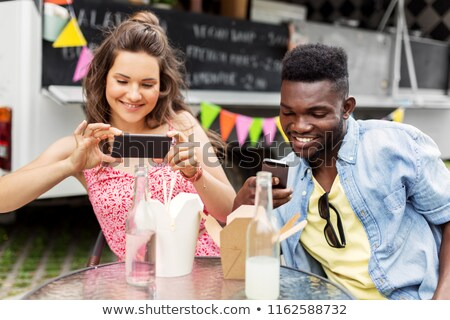 mixed race couple photographing wok at food truck Stock photo © dolgachov