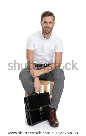 smiling young casual man sitts and holds briefcase down stock photo © feedough