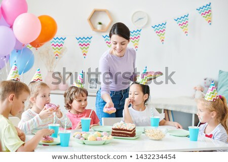happy young casual woman putting donut on served table stock photo © pressmaster
