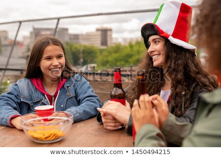 Cheerful pretty girls with drinks talking by table after football match Stock photo © pressmaster