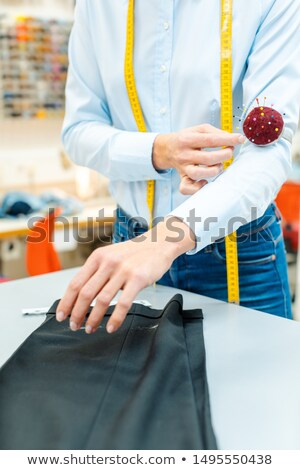 Alterations tailor working on some trousers Stock photo © Kzenon