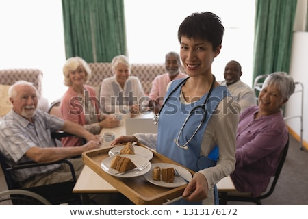 front view of young female doctor holding tray of cake with senior people waiting it around a table stock photo © wavebreak_media