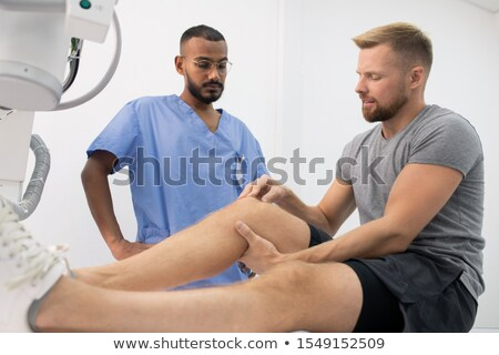 Young sportsman complaining on sick leg or knee while showing it to doctor Stock photo © pressmaster