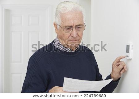Bezorgd senior man beneden centraal verwarming Stockfoto © HighwayStarz