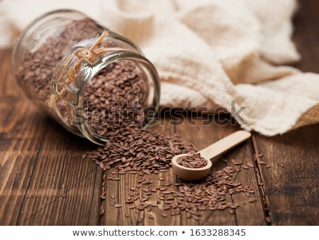 Glass jar of raw natural organic linseed flax-seed with spoon and linen cloth on wooden background.  Stock photo © DenisMArt