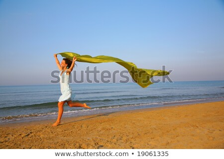 Young girl runs on edge of sea with yellow shawl in hands Stock photo © Paha_L