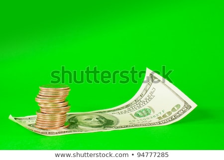 coins stacked in bars laying on stack of 100 dollar bill stock photo © andreykr