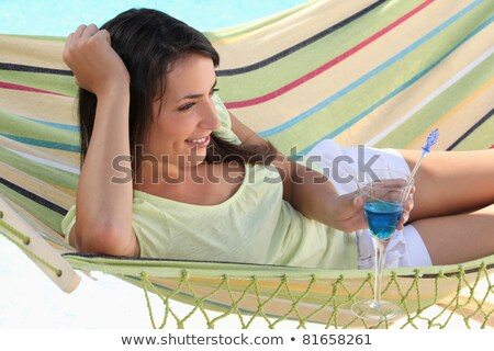 Foto stock: Woman Drinking Cocktail Whilst Lying On Hammock