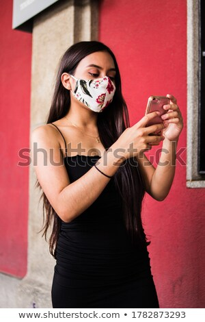 Young beautiful woman making self photo with her smartphone. Focus on phone. Stock photo © deandrobot