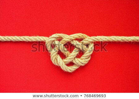 Heart shaped red knot on a jute rope isolated on white