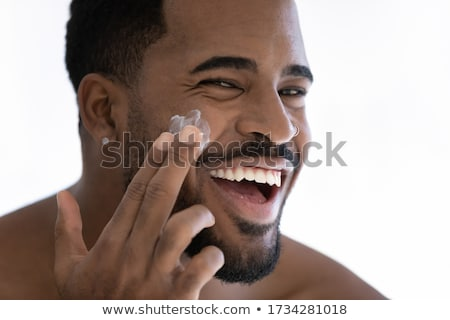 Young man putting cream lotion on face Stock photo © deandrobot