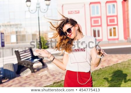 sorridente · feliz · mulher · ouvir · música · ao · ar · livre · estômago - foto stock © deandrobot