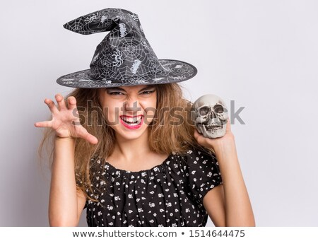 Beautiful witch holding human skull in her hand  Stock photo © Elisanth