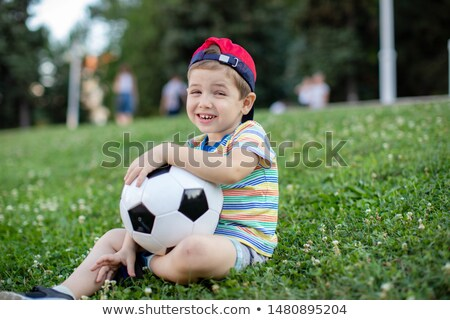 Boy is sitting on green grass with a soccer ball in his hand.Close up stock photo © Bigbubblebee99