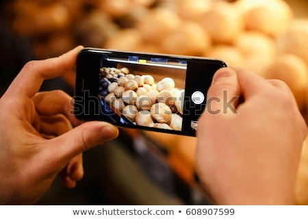 cropped picture of man make photo of bread in supermarket stock photo © deandrobot