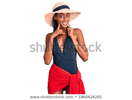 Portrait of cheerful smiling girl in hat and swimsuit pointing Stock photo © deandrobot