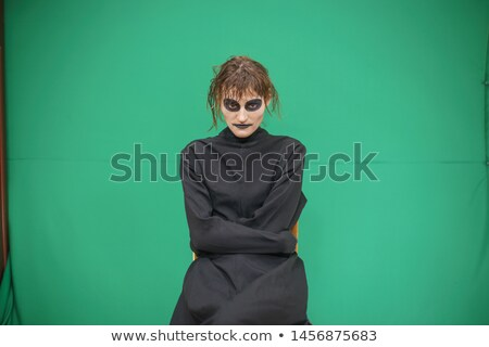 pretty brunette woman with make up like demon at halloween stock photo © iordani