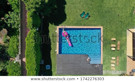 man floating on inflatable mattress in swimming pool stock photo © stevanovicigor