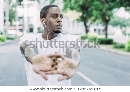 Portrait of a young concentrated sportsman stretching hands before workout Stock photo © deandrobot