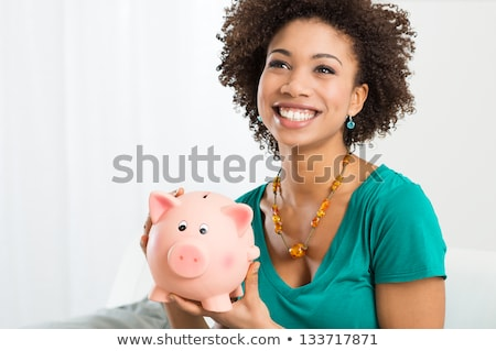 woman looking at piggy bank stock photo © is2
