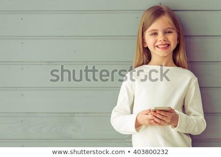 retrato · sorridente · little · girl · telefone · móvel · olhando - foto stock © deandrobot